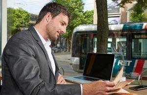 Man leest de krant terwijl de tram voorbij rijdt